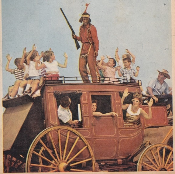 "Employees dressed in period costumes to lend an air of ""authenticity"" to the park's historical narrative. Here, a group of white visitors raise their hands in surrender to an employee dressed as a gun-toting Indian. NY Daily news Sunday Color Magazine, July 16 1961, pg. 27."