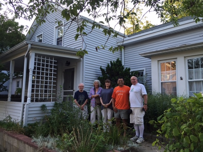 Whitman pilgrims Ken Smith (left), Ed Centeno and Frank Gagliardi (fourth and fifth from left) join historians Gail Horton and Margaret Guardi in front of 218 South Street, Greenport.