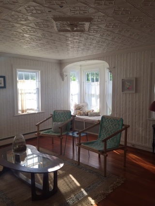 The living room on a sunny August morning. Note the intricately patterned tin ceiling and walls, as well as the picture window.