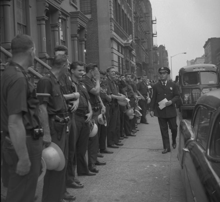 Officers in the nearly all-white police department line up in Harlem during the riot