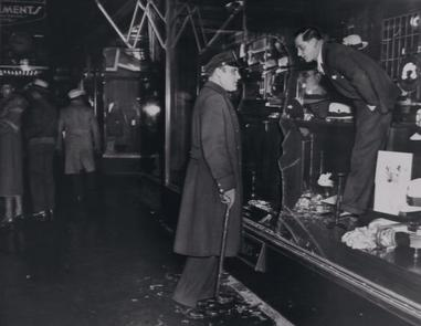 Store owner and a policeman survey a shattered plate glass window and the interior of the show window of a store at Seventh Ave. and 125th St. nights earlier