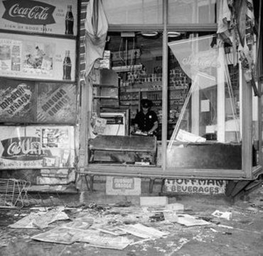 A police officer surveys damage in a looted Bed-Stuy store