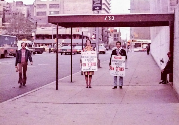 Philharmonic bassist Orin O'Brien and Philharmonic fourth horn Aubrey Facenda picketing outside Avery Fisher Hall at Lincoln Center.