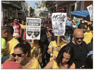 """Puerto Rican educators march in the streets of Old San Juan protesting Project 1456, which allows the fast-tracking of school closures and the requirement to open new charter-type schools. Their signs read """"We demand respect for school autonomy"""" and carry a sign of an imperial Uncle Sam."""