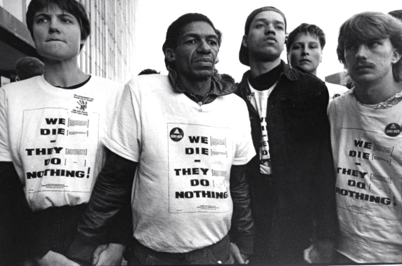 """Members of the ACT UP Majority Action Committee demonstrate at the Food and Drug Administration in Washington, DC in 1988. Their demands included that the drug approval process for AIDS treatments be shortened and that people from all affected populations, including women, people of color, poor people, and IV drug users, must be included in clinical trials. The t-shirts they designed and wore, """"WE DIE -- THEY DO NOTHING"""" list in fine print that WE = """"People of color, whether we are Afro-American, Native American, Hispanic, Latino, or Asian, women, men, IV drug users, partners of IV drug users, lesbians, gays, straights, the homeless, prisoners, and children affected by the AIDS crisis,"""" while THEY = """"Ronald Reagan, George Bush, Michael Dukakis, the NIH, the FDA, the U.S. Congress, the Congressional Black and Hispanic Caucus, our national media, our national minority leaders. The border repeats """"WE RECOGNIZE EVERY AIDS DEATH AS AN ACT OF RACIST, SEXIST, AND HOMOPHOBIC VIOLENCE."""" See footnotes for citation. Photo by and curtesy of Donna Binder."""
