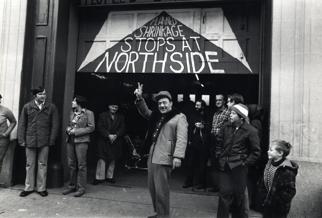 """In 1975-76, as New York City's fiscal crisis worsened, the head of of city housing development, Roger Starr, announced a controversial policy of """"planned shrinkage"""": the withdrawal of police and fire stations and the closure of schools, hospitals, and subway stations in poor and non-white areas of the city. Firehouse 212 was slated for closure by the city; beginning on Thanksgiving Day, 1975, Northside residents occupied it for 18 months in a civil disobedience campaign aimed at stopping the cuts. They painted this mural on the Firehouse door.  Photograph by, and courtesy of, Janie Eisenberg."""