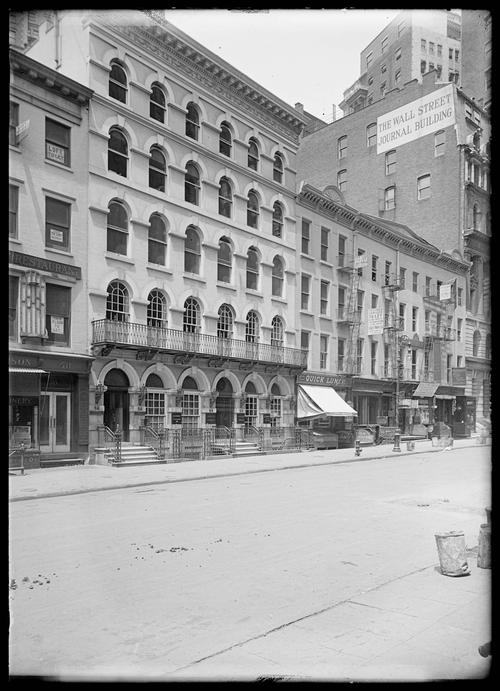 """View of Broad Street, undated (c. 1900–1919): Robert L. Bracklow Photograph Collection, New-York Historical Society. This view of Broad Street depicts (on the right hand side of the image) the entrances to a """"quick lunch"""" establishment and the Exchange Buffet, the first self-service restaurant in New York City—the kinds of eating establishments that would have come to mind when the """"rushing lunch-counter"""" was invoked."""