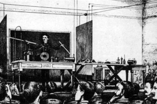 """Tesla demonstrating his wireless lamps at Columbia University, May 1891. From """"Experiments with Alternate Currents of Very High Frequency and Their Application to Methods of Artificial Illumination,"""" Electrical World, 11 July 1891, pp. 18-19."""