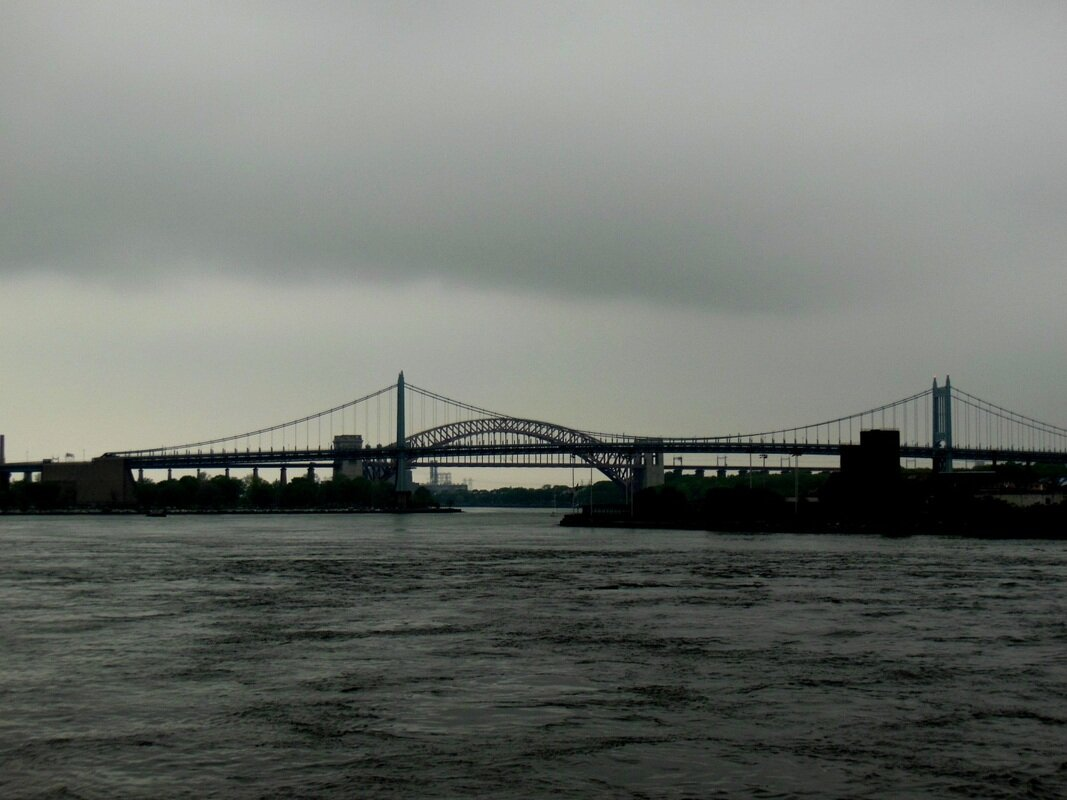 Hell Gate today, from Carl Schurz Park at about E. 88th Street, looking northeast toward the narrow channel between Hallett's Point in Astoria on the right and Ward's Island on the left. The rocks that used to be here would have occupied much of the river in the foreground. The dichotomy today is no longer heaven and hell, but the countervailing arches and cabling of the Hell Gate and Triborough bridges. (Photograph by the author.)