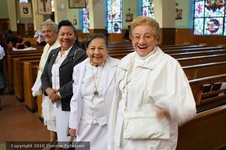 """Women at St. Michael's Church in Flushing, Queens, prior to the start of the """"La Naval de Manila"""" procession and ceremony"""