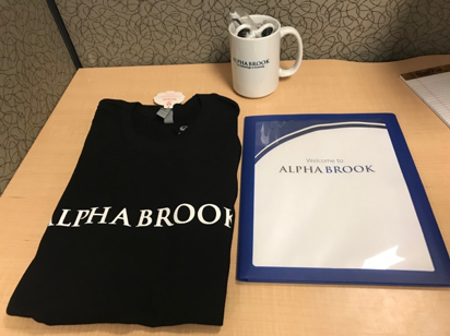Employee Welcome Packets include a company shirt, mug, and folder with the AlphaBrook branding.