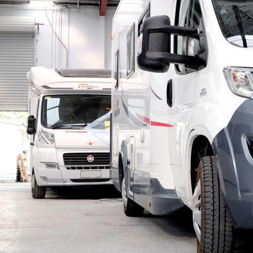 two campervans in a large workshop