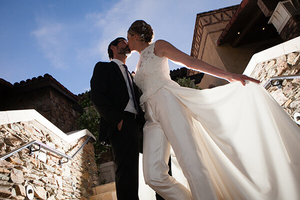 Groom-and-Bride-kissing-in-custom-made-white-bridal-suits-with-maxi-skirt-around-the-waist.jpg