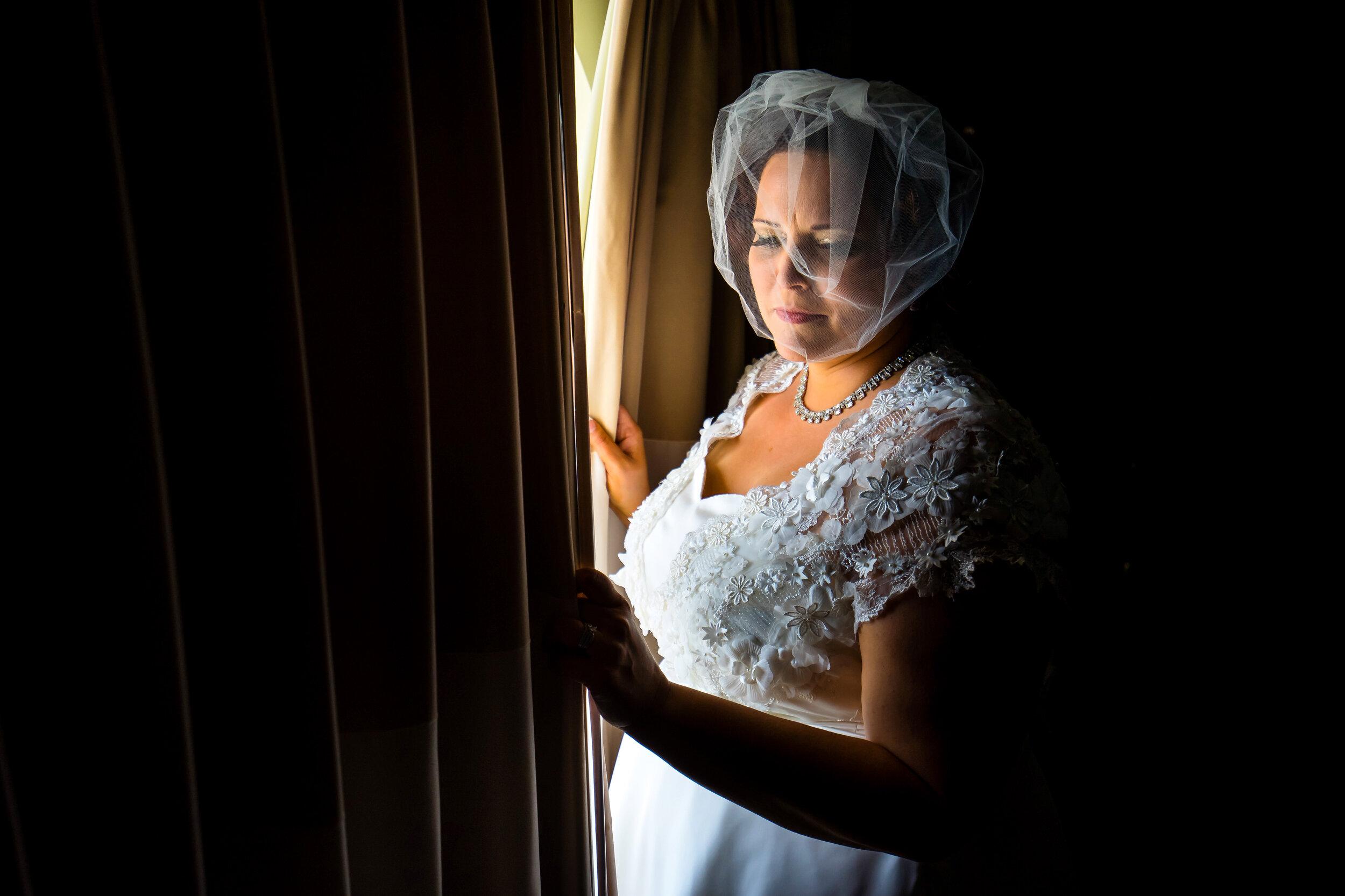 Vintage bride in bespoke wedding dress with net fascinator opening the curtain.jpg