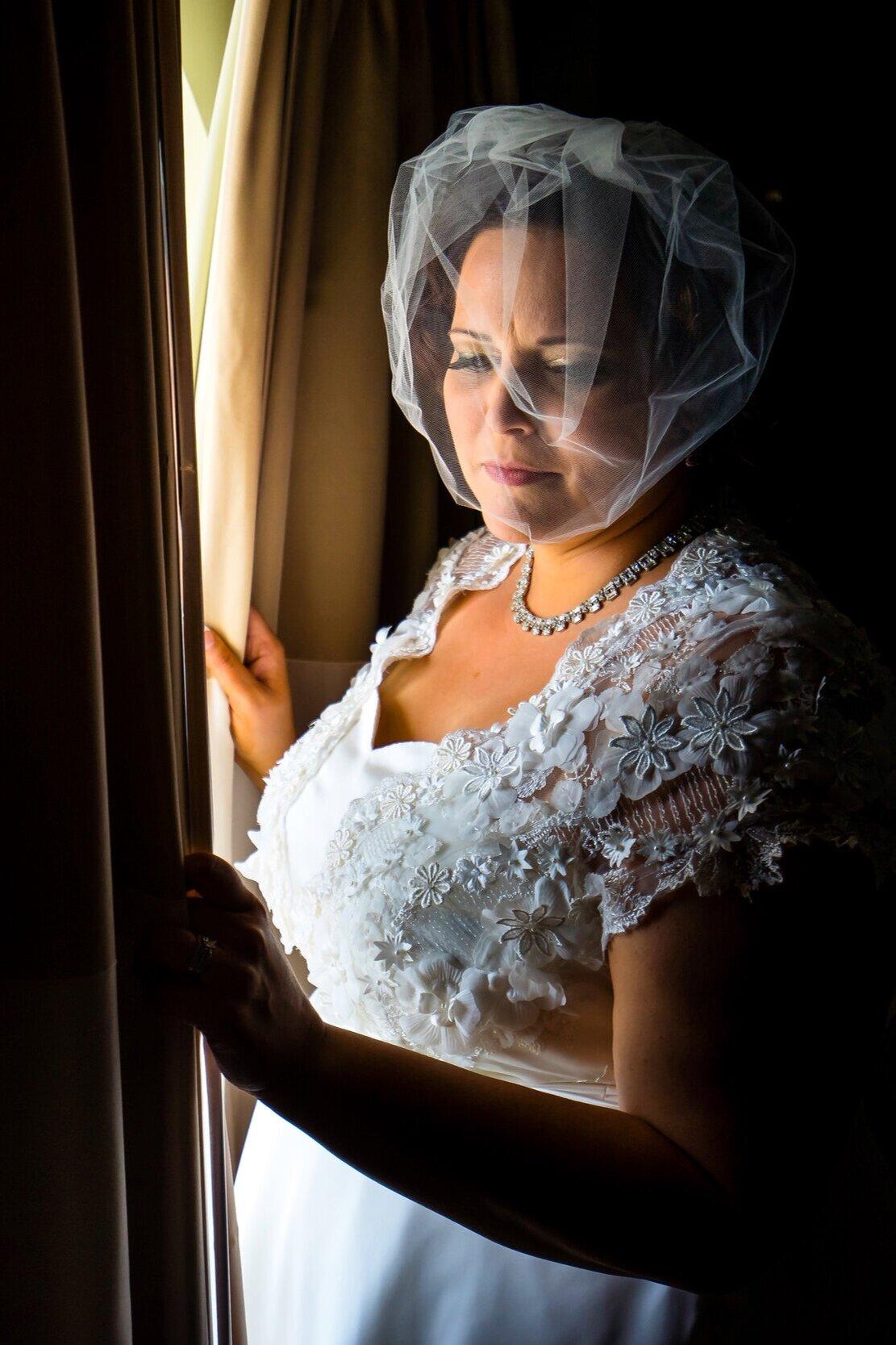 Vintage+bride+in+bespoke+wedding+dress+with+net+fascinator+opening+the+curtain.jpg
