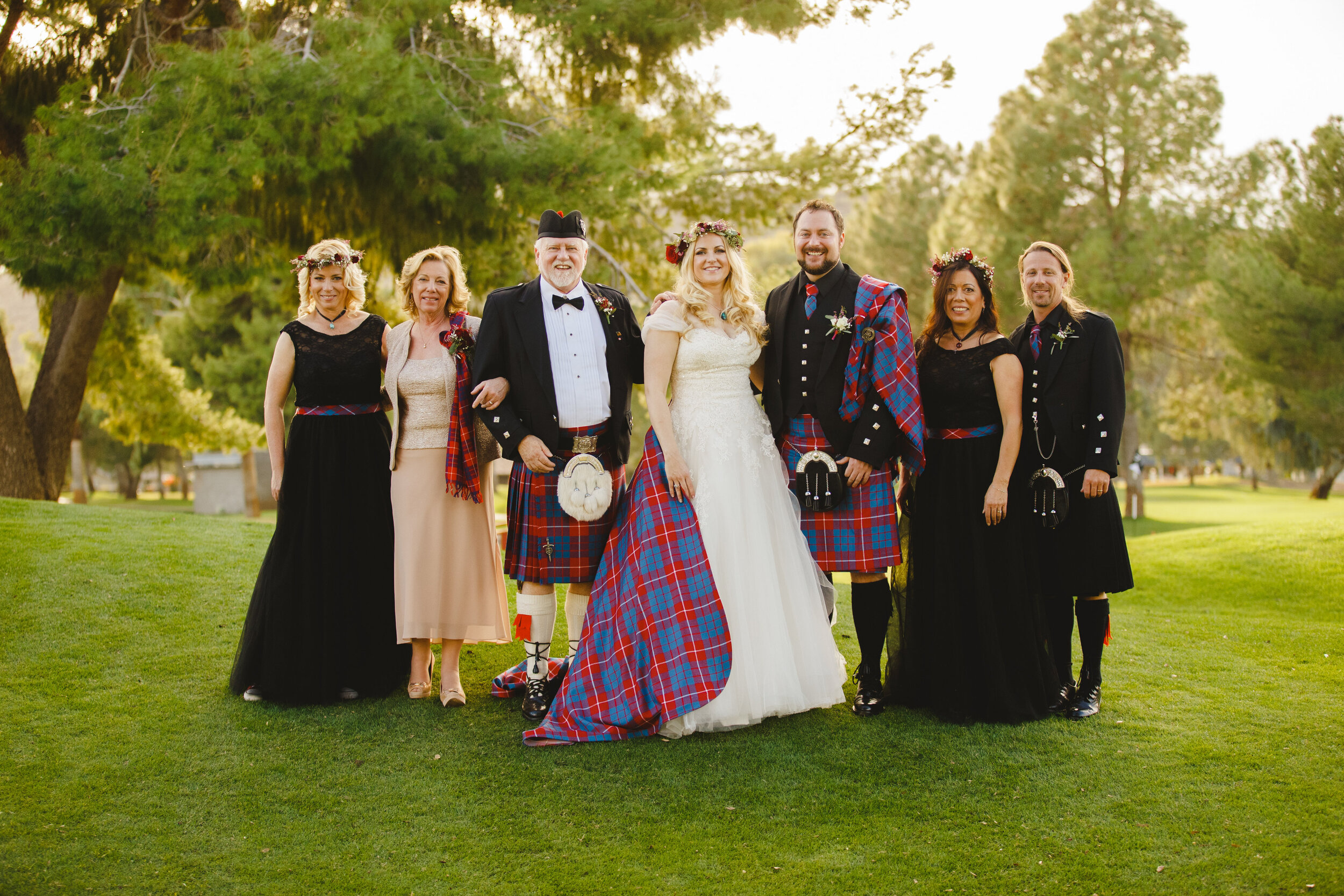 Bride and groom in Scottish traditional kilt highland dress with their parents portrait photography with redesigned detachable Scottish tartan train.jpg