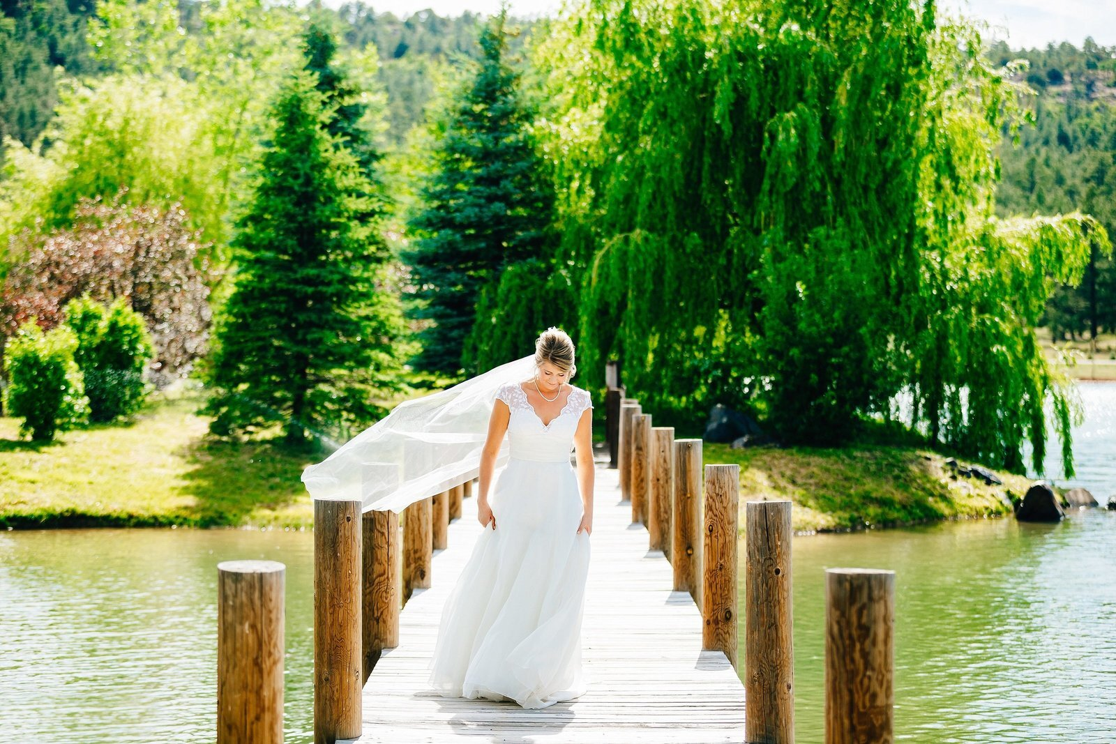 Bride in heirloom 50s vintage wedding dress from grandmother walking in the wood bridge of the river.jpg