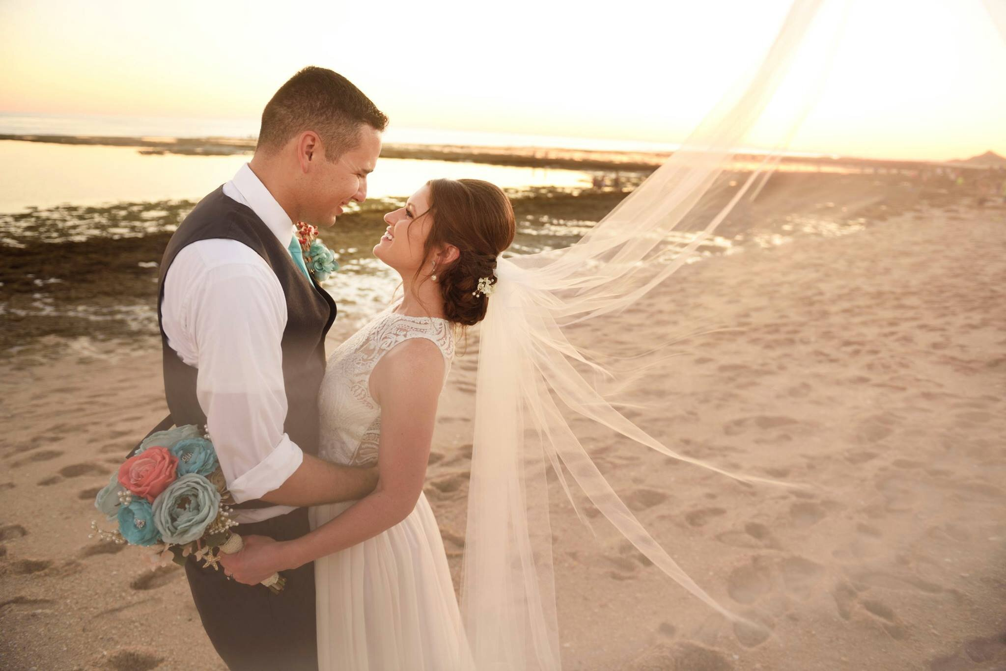 Bride and groom holding each other in bespoke lace wedding dress at beach resort wedding and long wedding veil.jpg