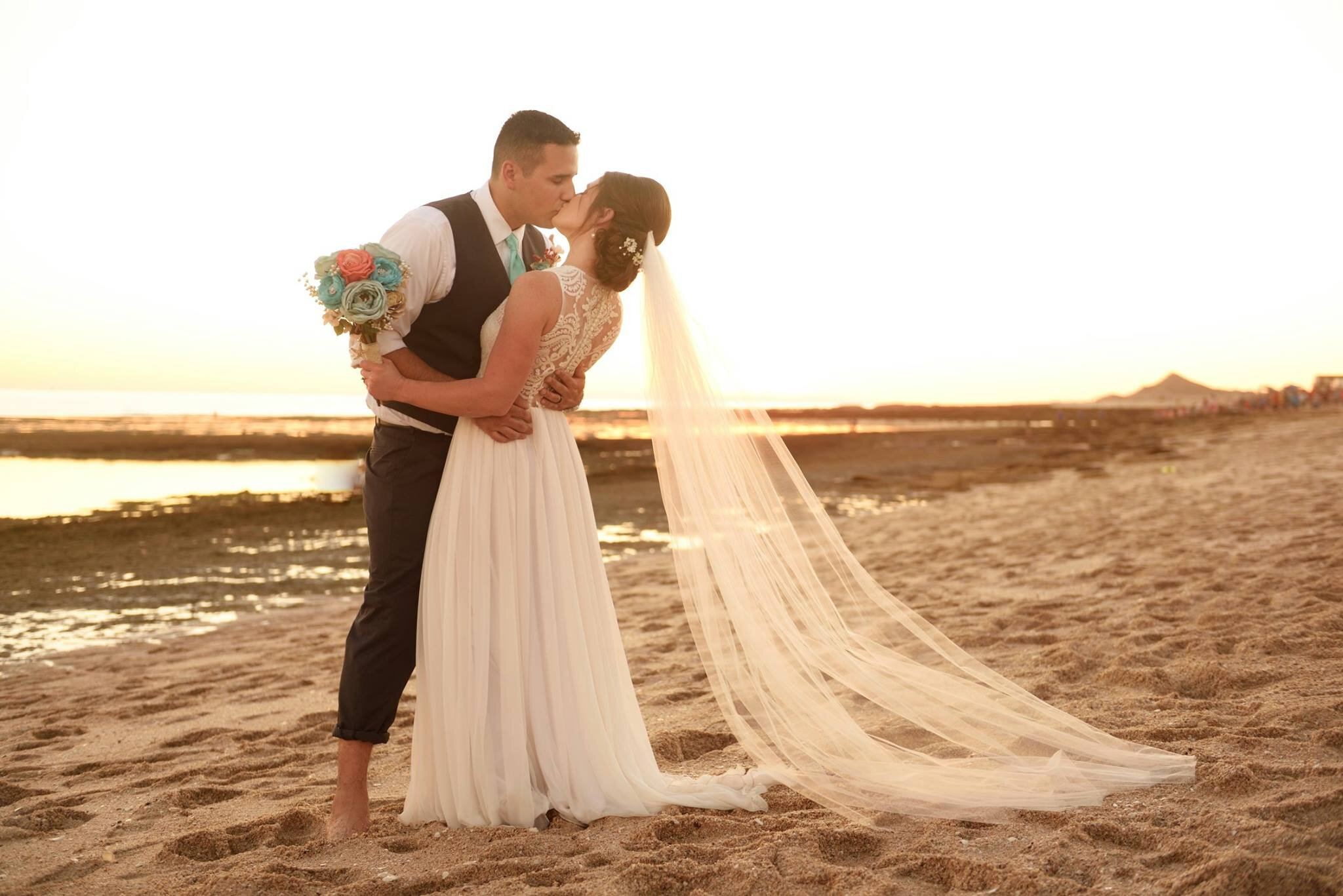 Bride and groom kissing at the beach wedding wearing bohemian lace custom made bridal gown with long veil.jpg