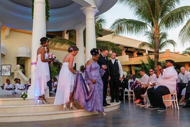 Bride and groom walking down the aisle wearing custom made purple long bell sleeved wedding dress.jpg