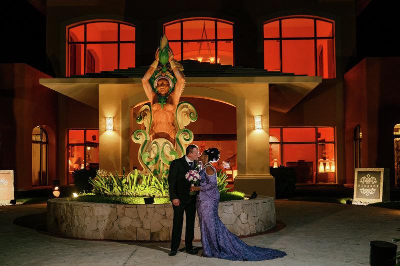 Bride and groom wearing a purple open shoulder wedding dress for Mexican resort hotel wedding.jpg