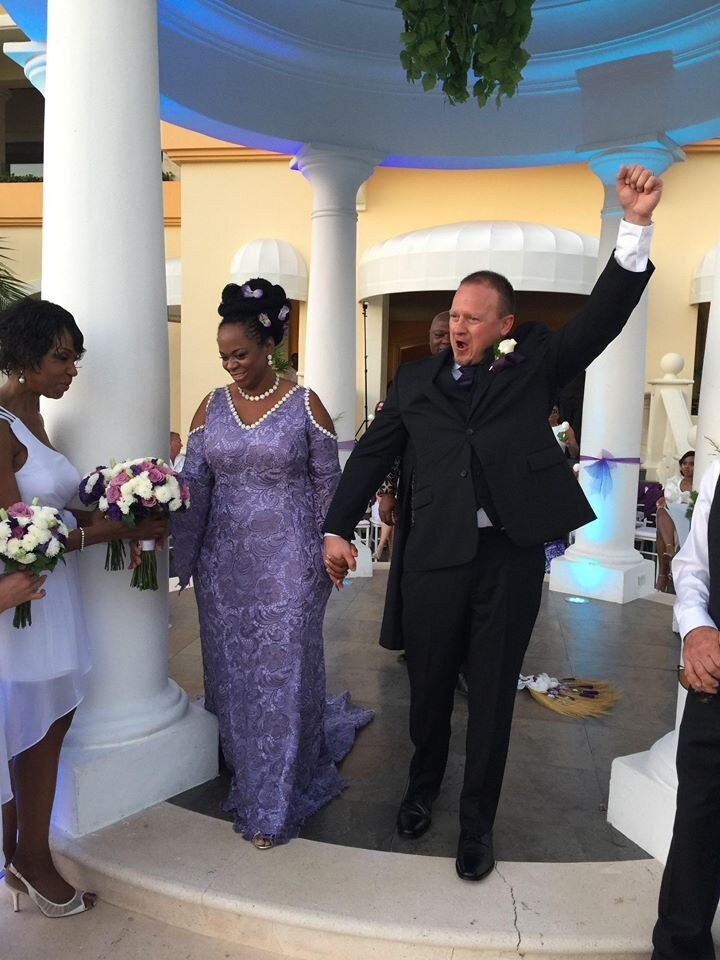 Bride and groom wearing a purple lace modest wedding dress accented with pearls.jpg