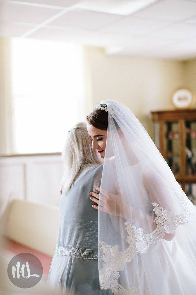 Bespoke bride wearing one of a kind lace trimmed wedding veil hugging with mother of the bride.jpg