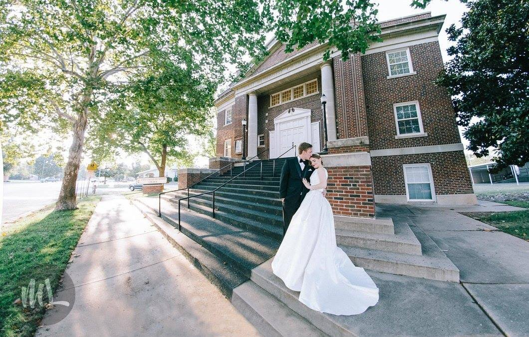 Bride and groom in front of the chapel wearing bespoke couture wedding gown.jpg