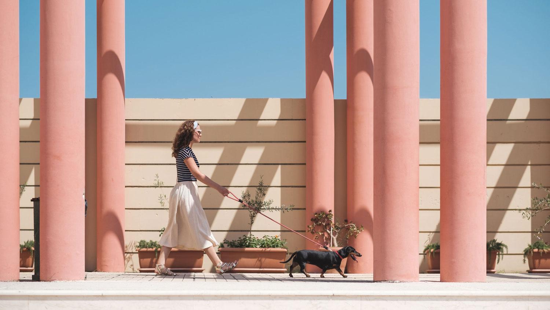 Woman in boho skirt walking her dog among pink columns