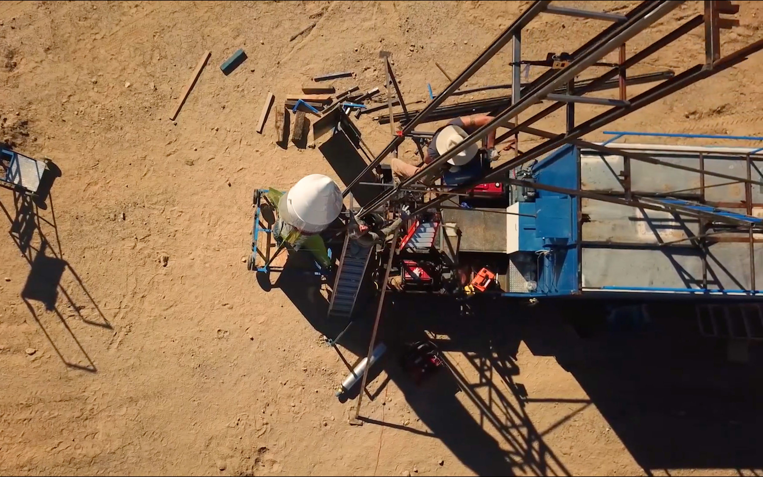 Waldo Stakes climbs up the rocket launch ramp to secure a welder to use as 'Mad Mike' watches from below.