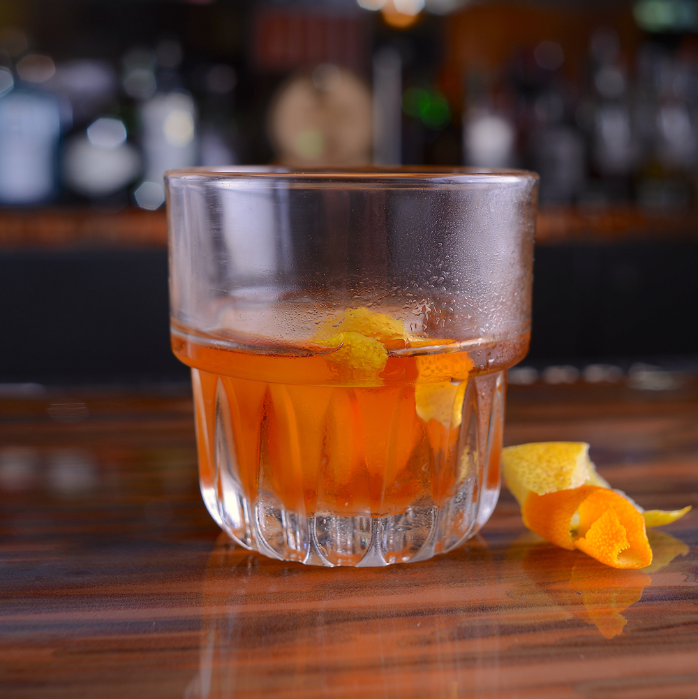 Old Fashioned - Our classic Old Fashioned. A sugar cube soaked in bitters, whiskey, served in a tumbler with one giant ice cube. We garnish with a twist, and we express the oils from an orange peel by flaming it with a wooden match.