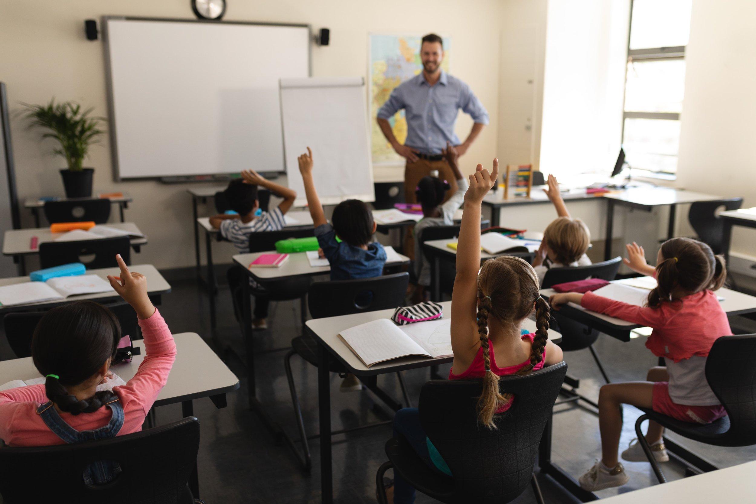 rear-view-of-school-kids-raising-hand-in-GCUXYHR-min.jpg