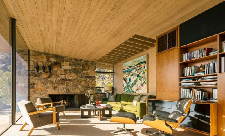 02-The-living-room-features-a-natural-wood-ceiling-with-beams-s-tone-clad-wall-with-a-fireplace-and-a-fine-selection-of-comfy-mid-century-furniture-775x470.jpg