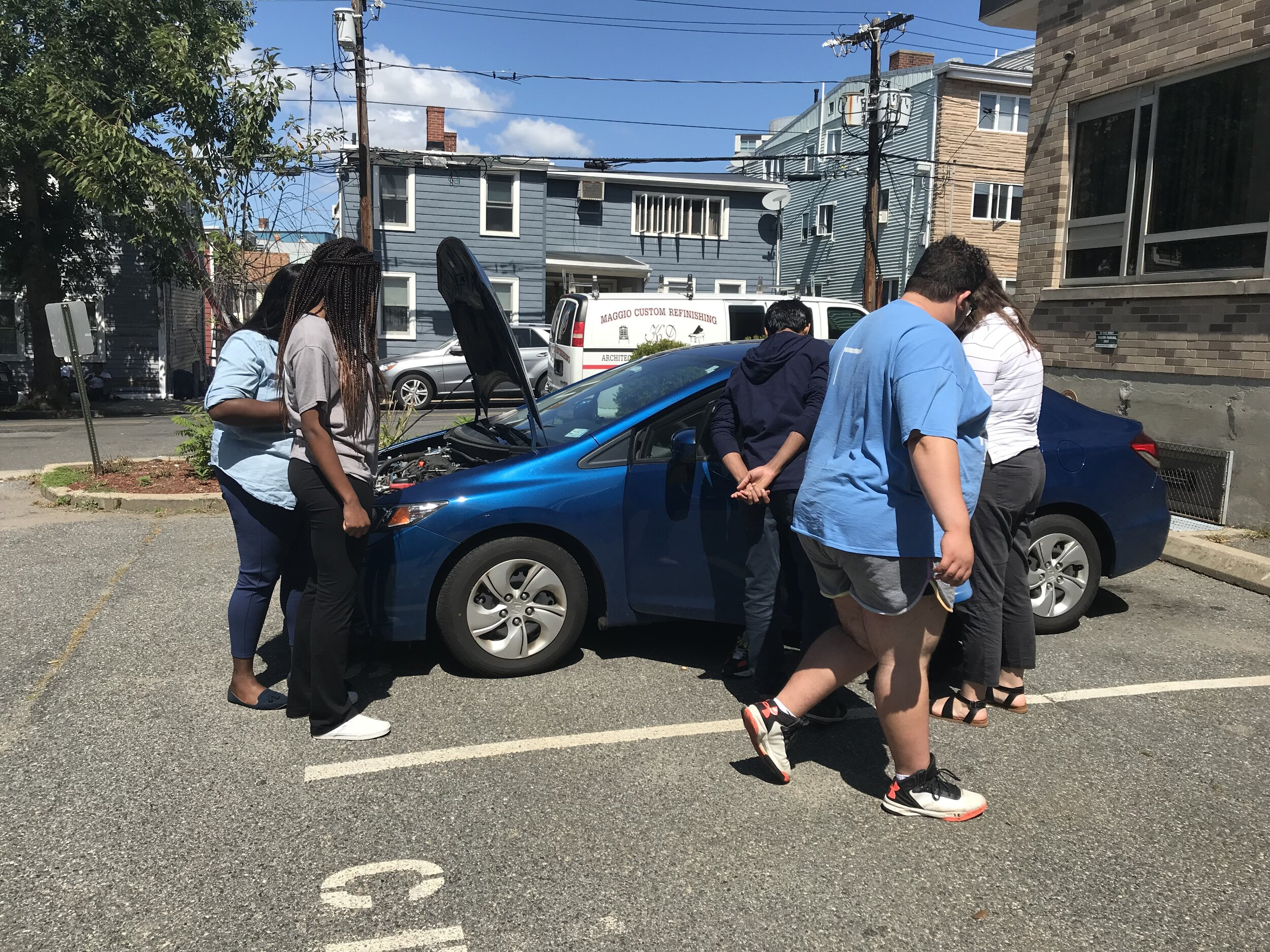 Youth in foster care and IFC social workers inspect a car and learn how to check oil.