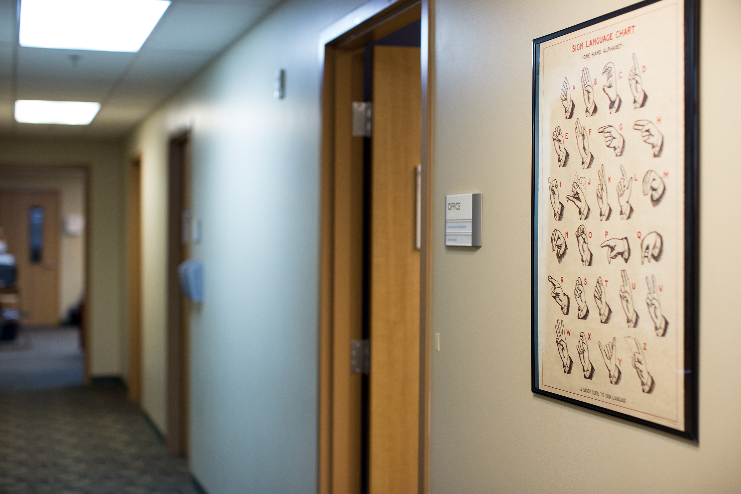 Picture of an office hallway with a framed poster of the alphabet is American Sign Language.