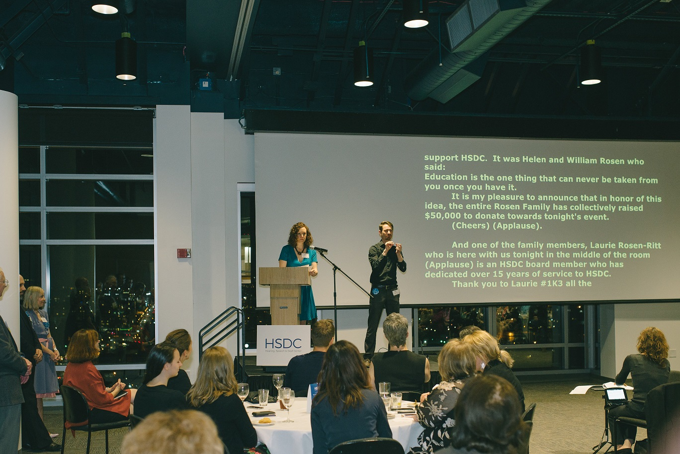 Photo from an HSDC's fundraising event. Audience is sitting at round dining tables with a speaker at the podium. On stage with the speaker is a working Deaf Interpreter next to a screen with the evening Real Time Captioning transcript being projected.