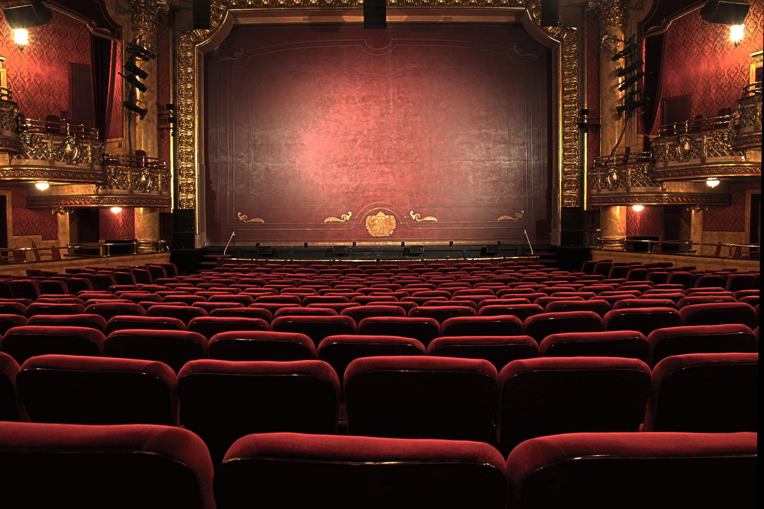 Photo of an old theater hall with red seats and a red curtain.