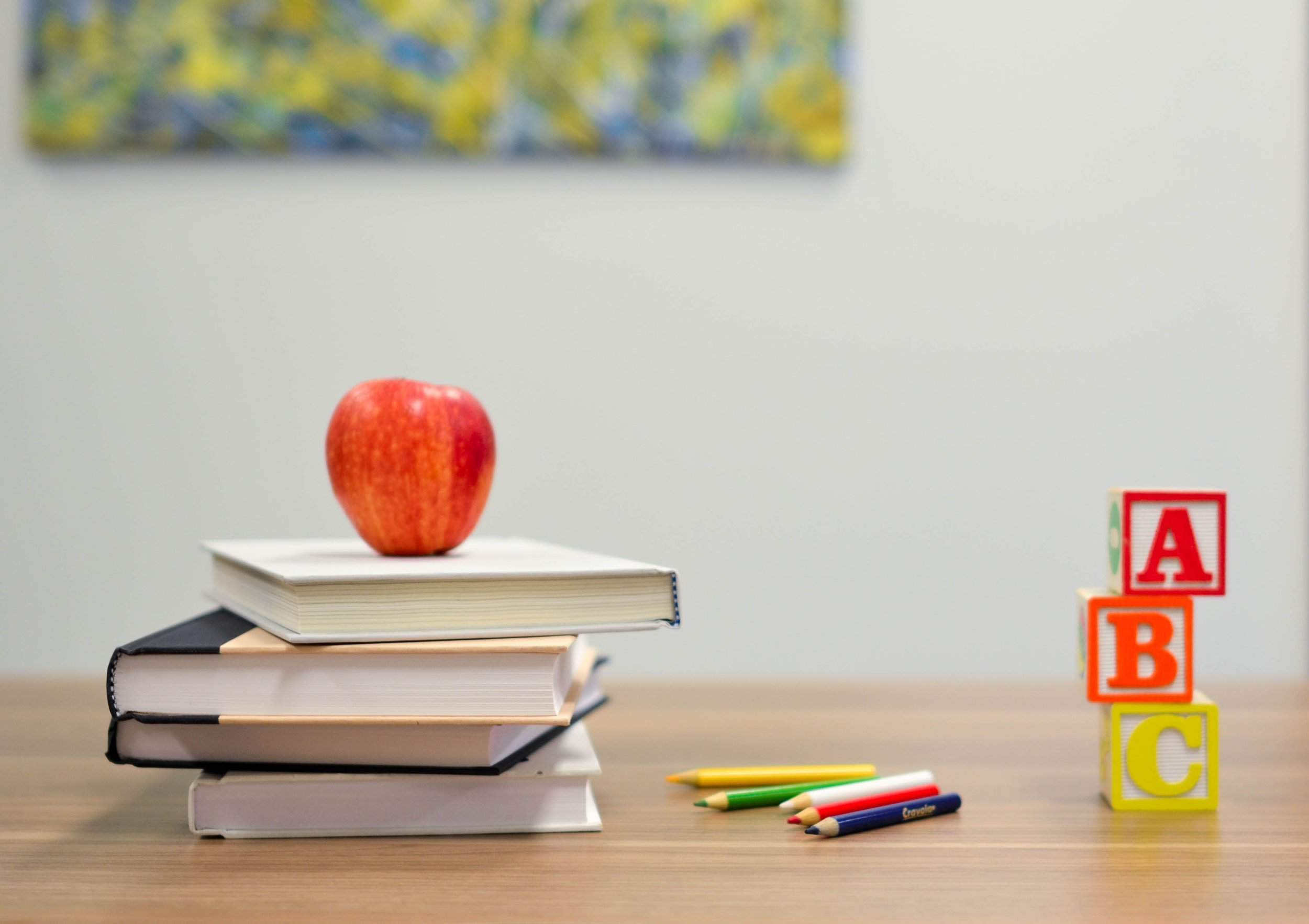Photo of a wood desk. On top is 4 school books with a red apple on top, colored pencils, ABC blocks stacked.