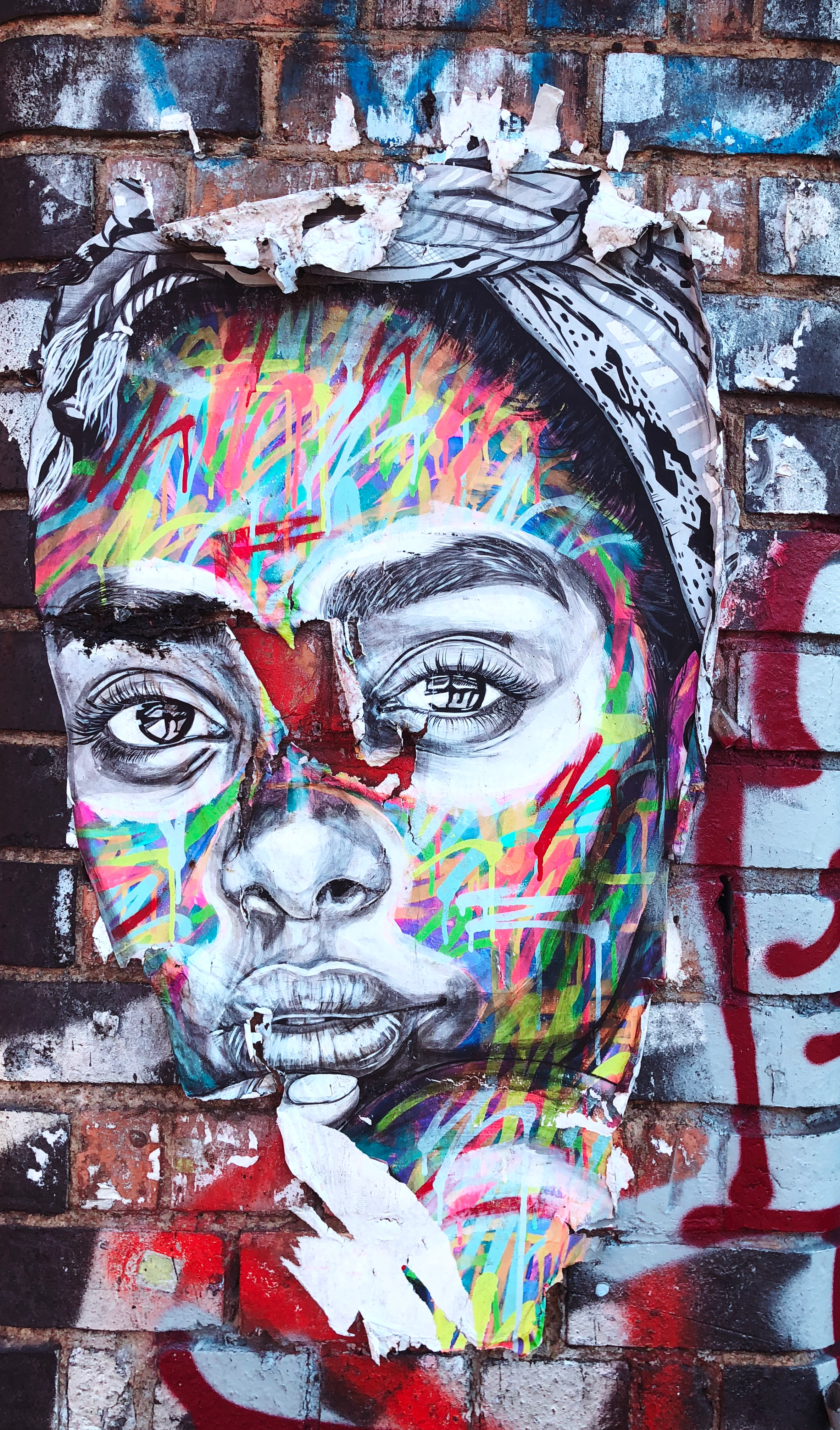 Graffiti art on a brick wall which is the face of a woman.