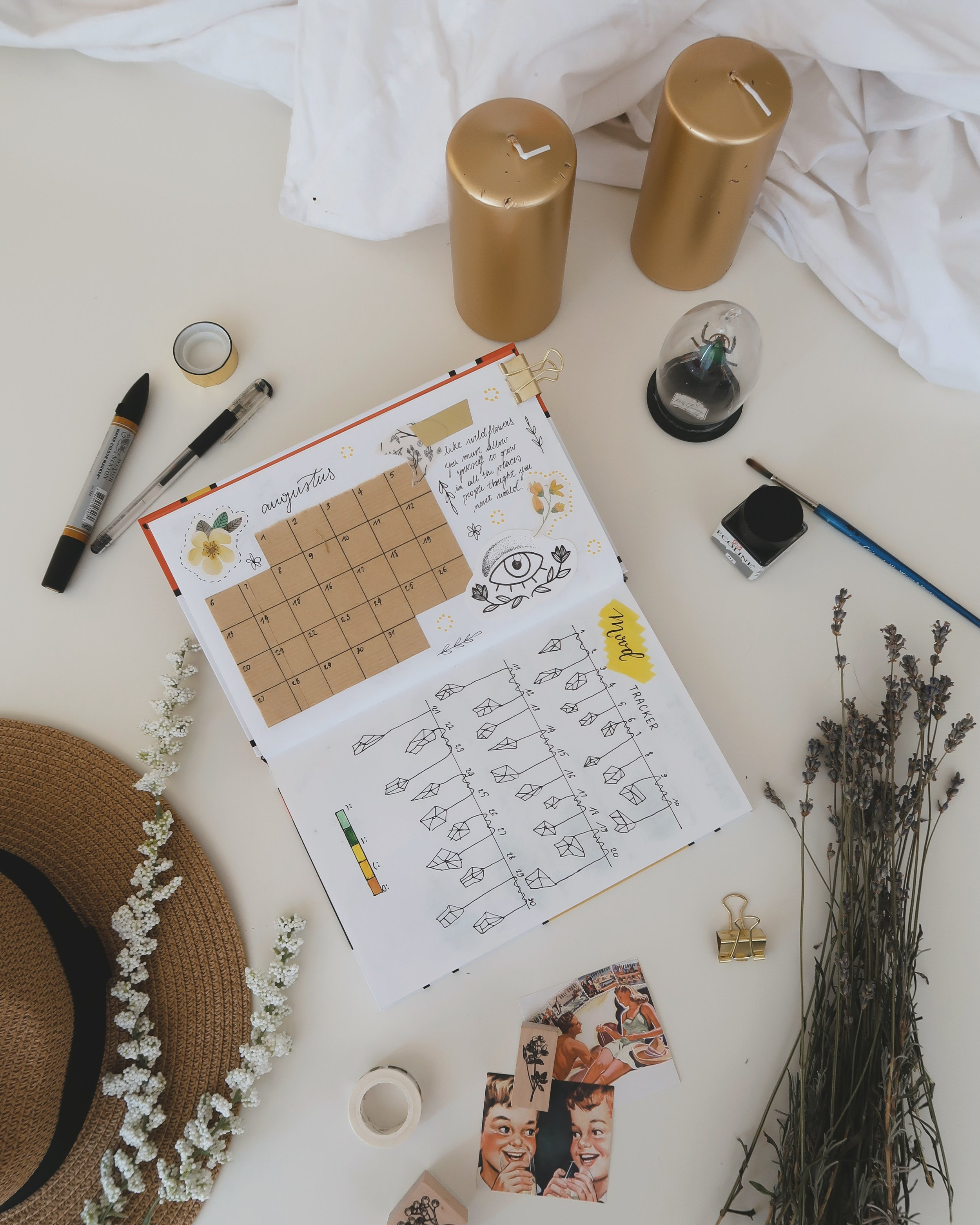 Photo looking at the top of a desk with pens, a scrape book with handmade calendar and drawings, lavender flowers, hat, paint brush, beetle in a case.