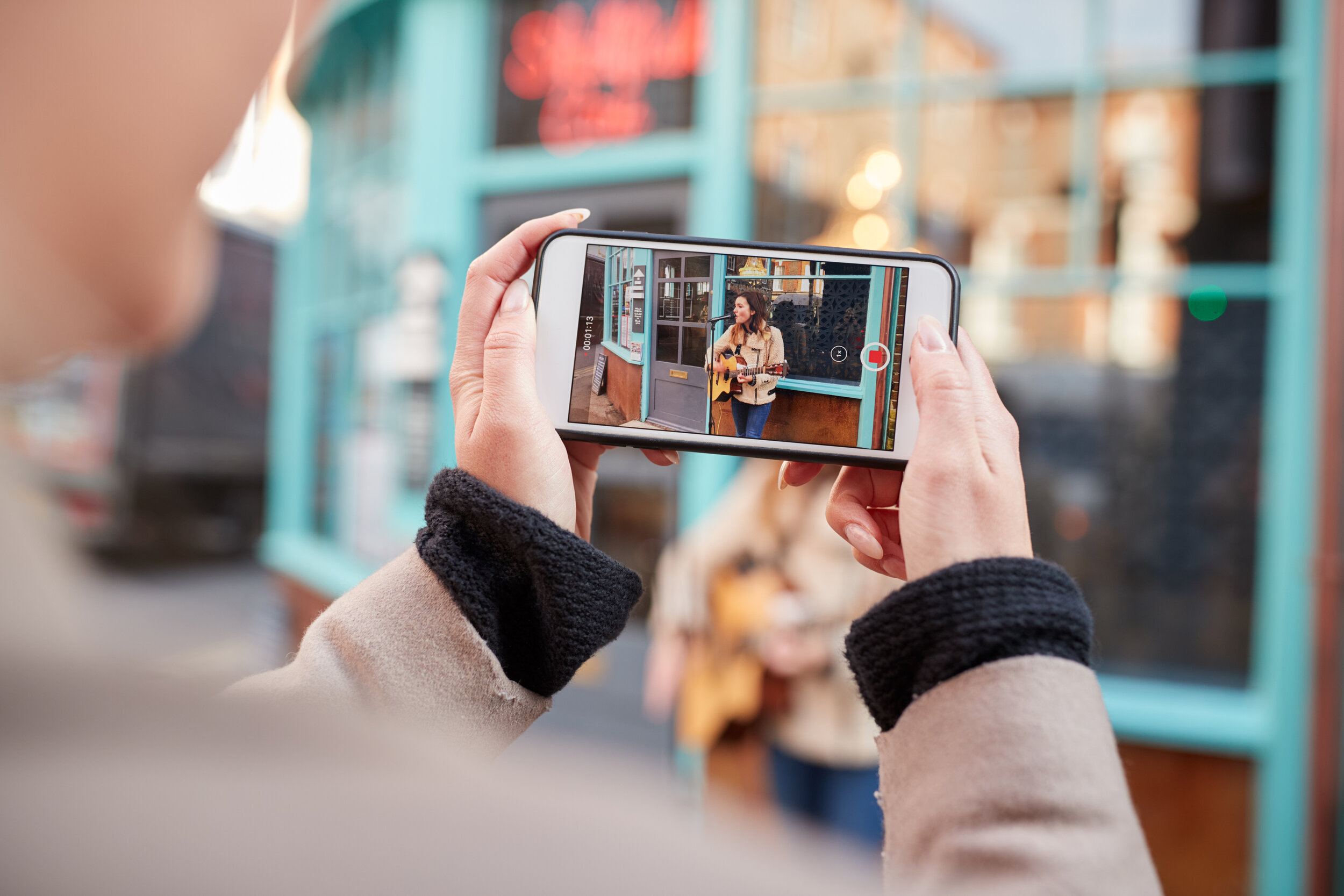 person-filming-female-musician-busking-playing-aco-7ZDHS3N.jpg