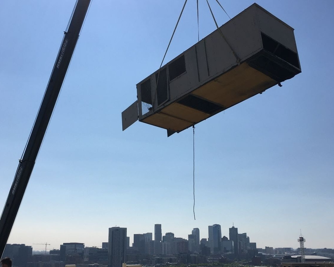 One of two original rooftop units being removed from the roof of 2727 Bryant, as part of their C-PACE project. LONG Building Technologies was selected for all the HVAC-related repairs, as well as for installation of the building control system. (Photo credit: LONG Building Technologies)