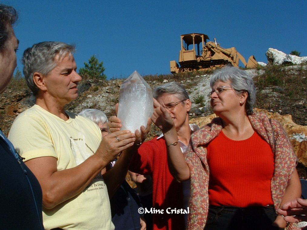 The guide helps visitors examine a big crystal.