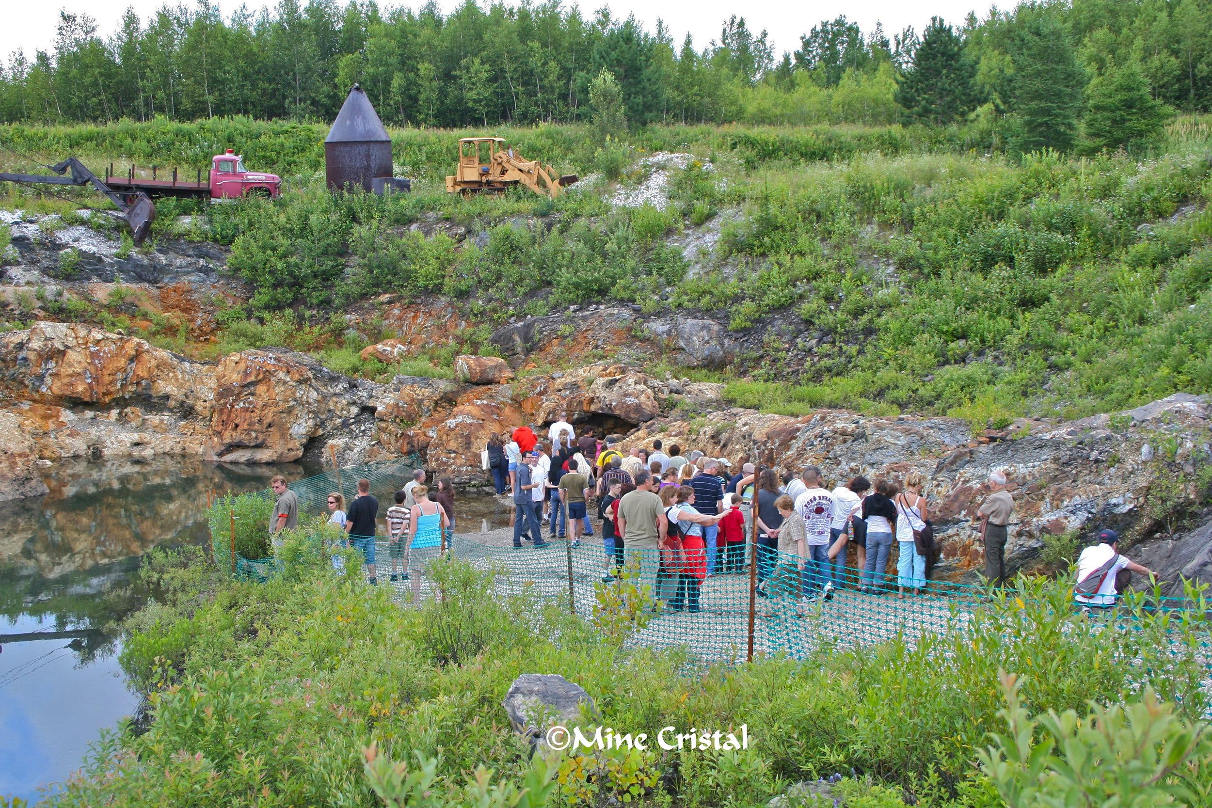 Les participants à la visite examinent notre mine de cristal et admirent le site géologique unique. Une veine de quartz blanc massif avec des cristaux scintillants.
