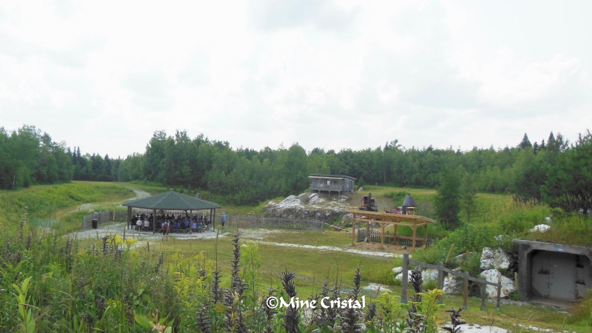 Le guide parle des cristaux aux participants assis sous un belvédère à la mine.