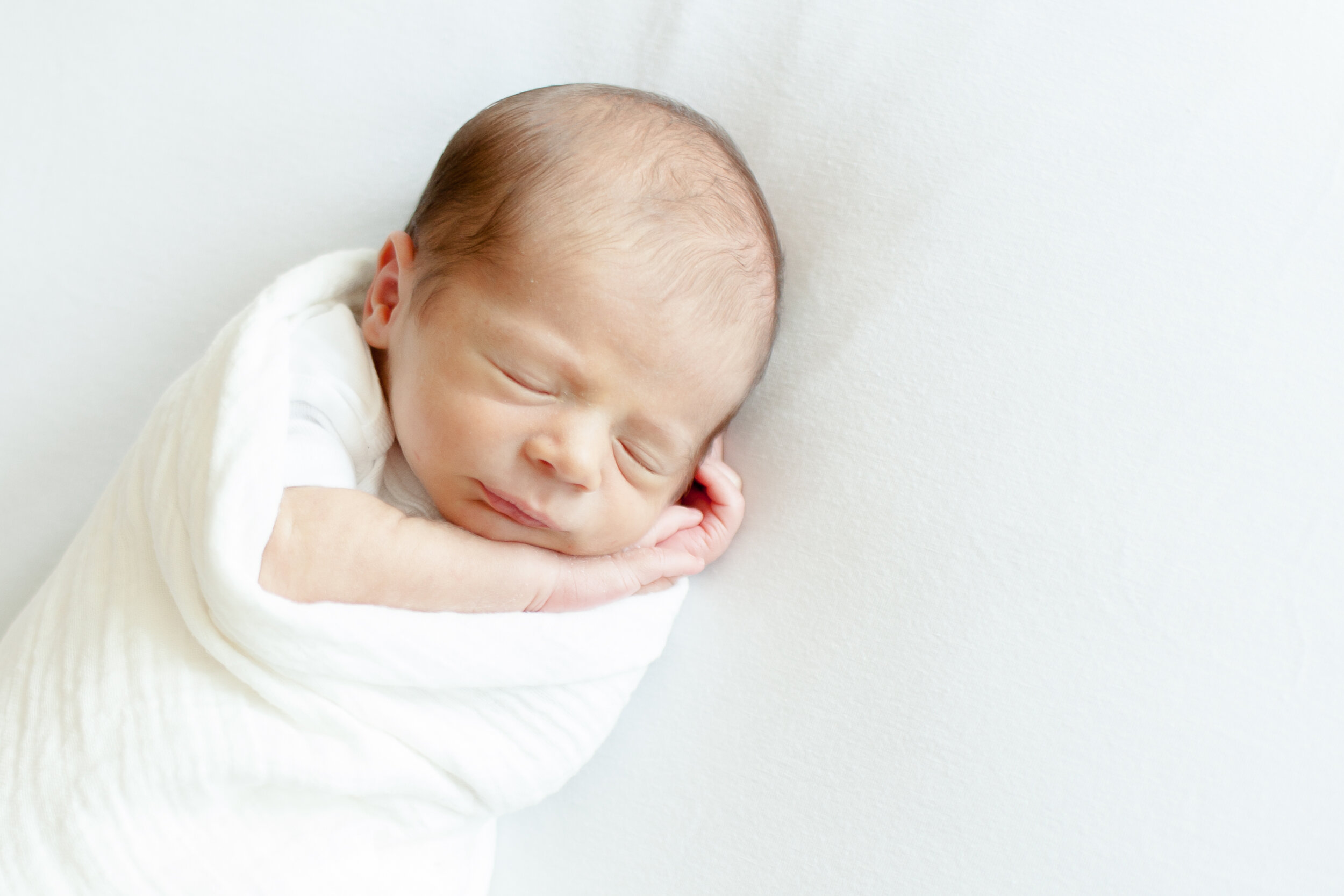 Newborn baby swaddled in white blanket with white background in natural lighting.