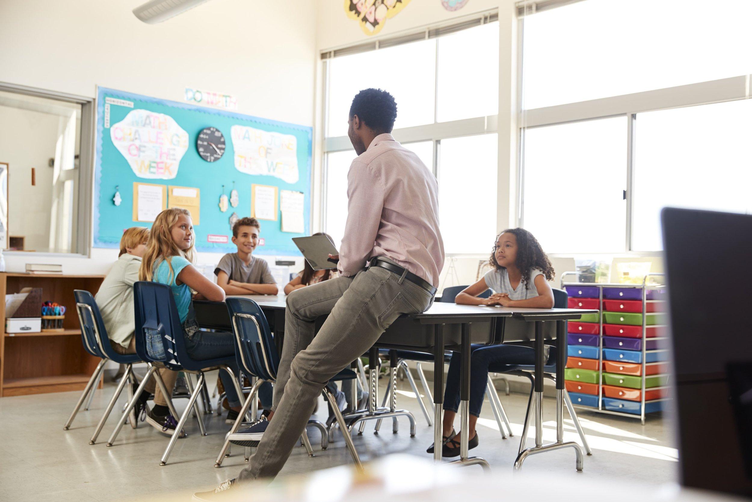 male-teacher-with-elementary-school-kids-in-7YBX4JM-min.jpg