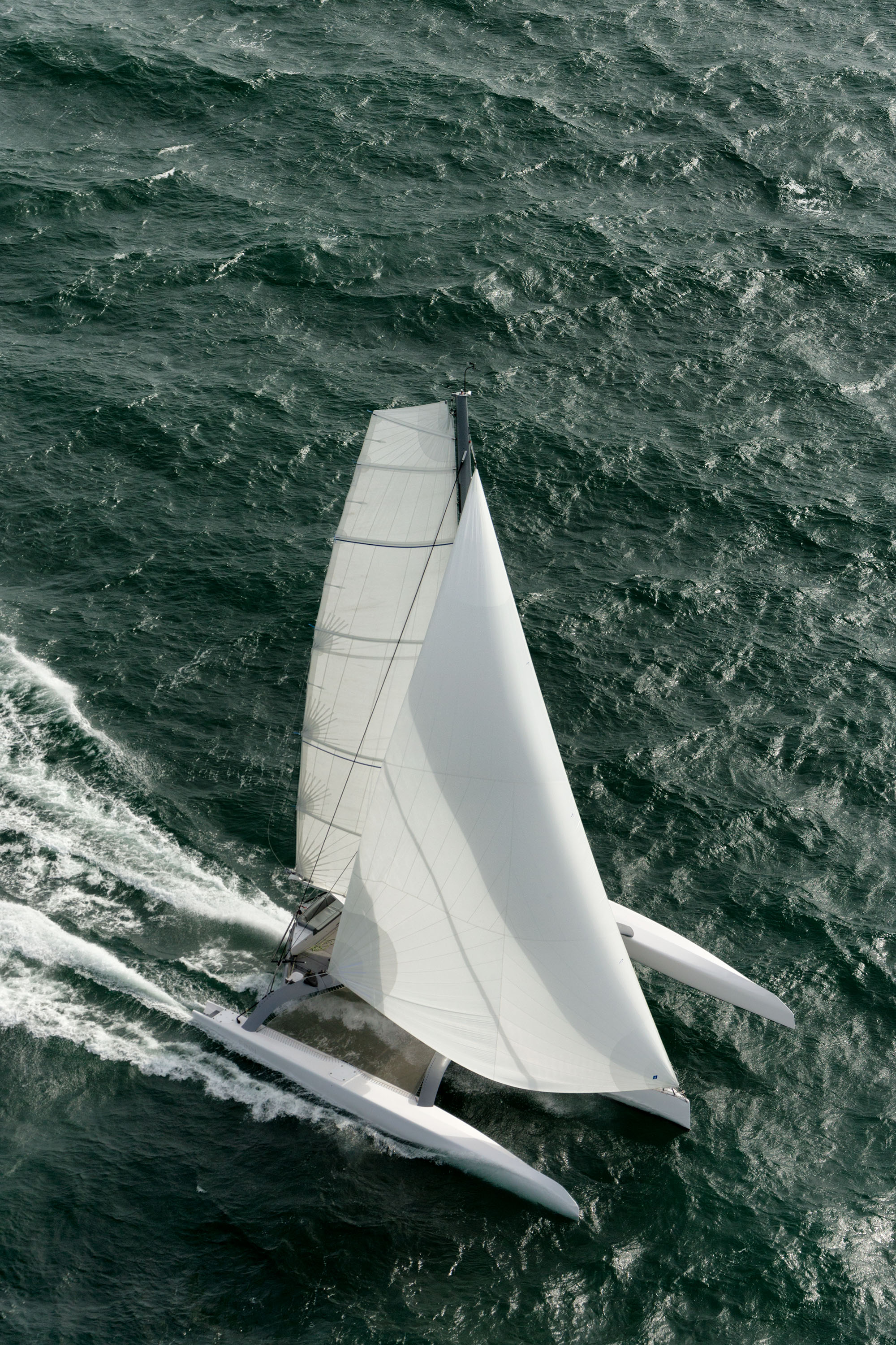 Balance - A trimaran provides the greatest righting moment between monohulls, catamarans, and trimarans.A properly designed trimaran will give you the most stable platform in any sea state.A monohull's response to wind is to heel first and then move, spilling power initially. Unlike a catamaran which carries its mast on an unsupported bridgedeck, a trimaran carries its mast is on the main hull.Since the windward ama on a trimaran is always flying, this additional leverage provides valuable righting moment when power reaching and in gusty conditions.Therefore, the response of FINN with the additional advantage of a canting rig is to heel less and go more.