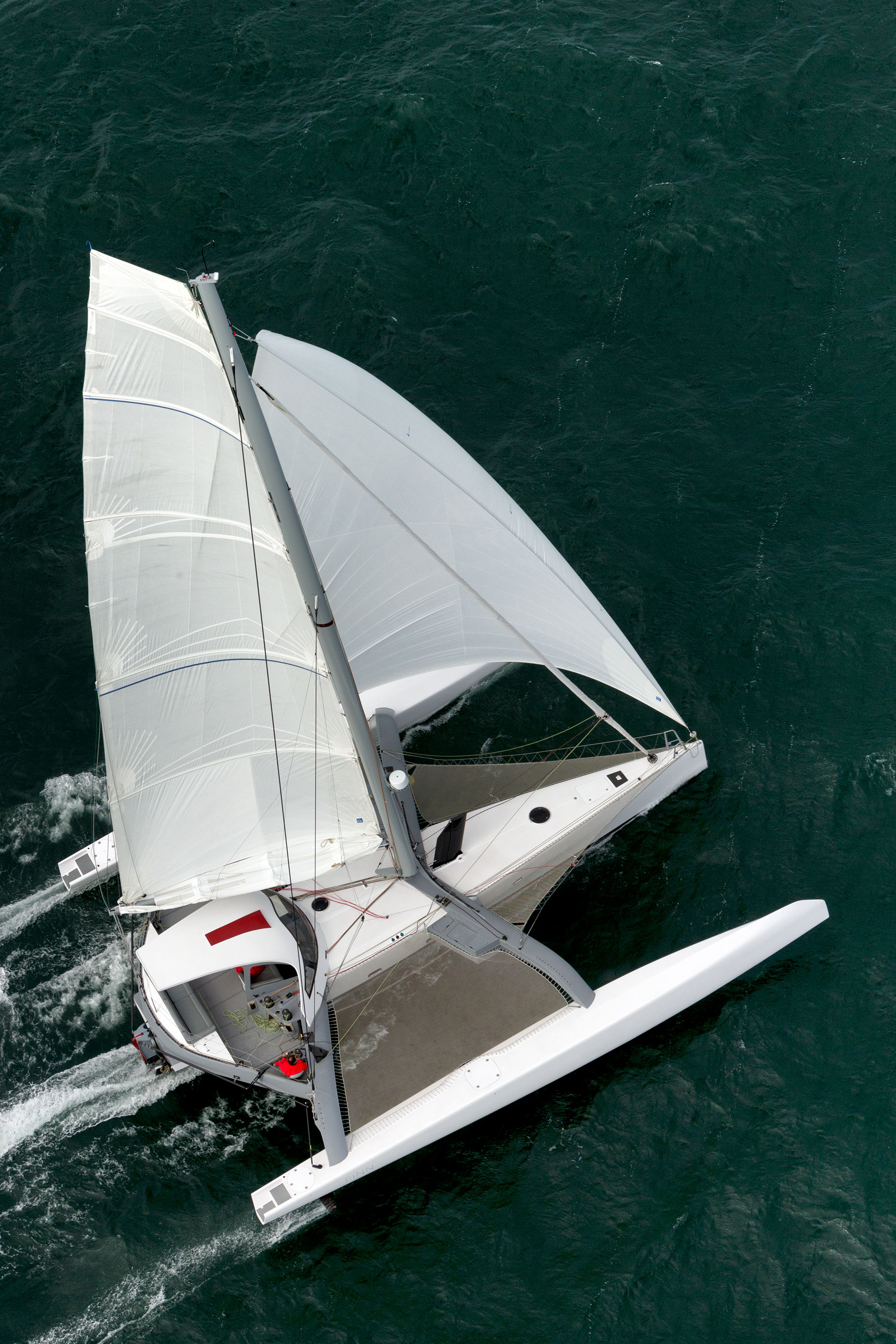 Sailboard-inspired rig - We have all seen sailboards with their masts raked back and windward and the sailors weight well aft. FINN does the same thing.With a rotating and canting Lorima high modulus carbon spreader-less rig, and an aft ballast tank, the trim and righting moment are greatly enhanced. During a tack, touch a button at either helm pod and the hydraulic ram releases the rig to drop to leeward. Push the tiller over and release the mast rotation and you come out of a tack in less than half a boat length with very little loss of speed.Spreaders are a failure point. Each turnbuckle is a failure point. They are a pain in the ass to tune. Take a traditional rig off and you will spend days tuning the rig, often with professional help. I can't thank Bruno and Renaud enough for advising me to do a spreader-less rig. It is possible because of the large beam of a trimaran. It's not only bomb-proof, its always in tune. The two shrouds meet and then join to spectra which is connected to a ram on the aft side of the aft crossbeam. When one ram lets out, the other pulls in. To cant, the rig is either dropped before tacking, or pulled hydraulically while sailing with the press of a button on the nav pod. This same setup allows the rig to come off the boat in minutes by pulling the three large terminal pins. Its simple and robust, a characteristic of French racing designs.