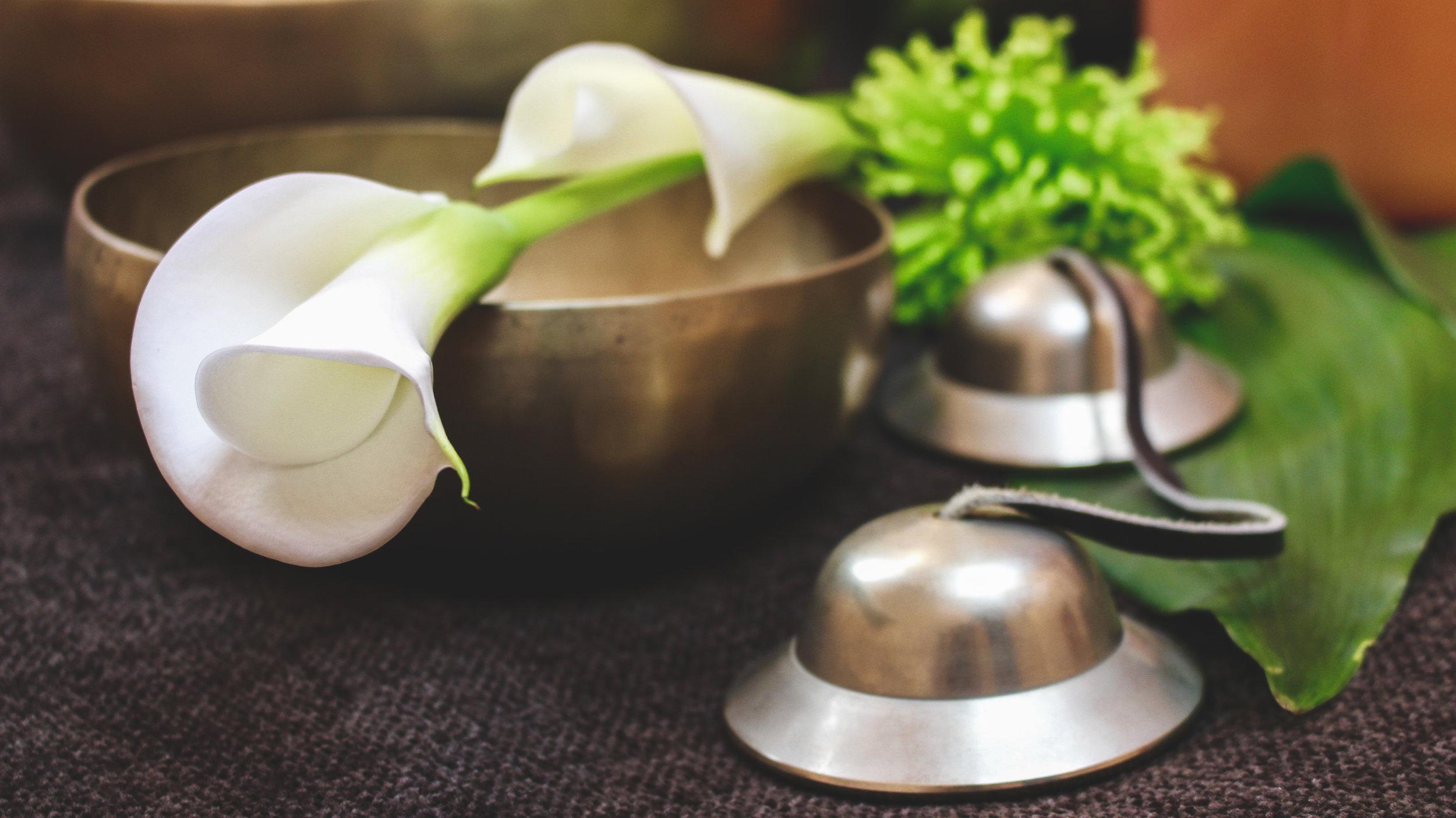 Blume und Klangschalen auf grauer Decke